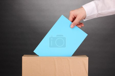 Photo pour La main avec le bulletin de vote et de la zone sur fond gris - image libre de droit
