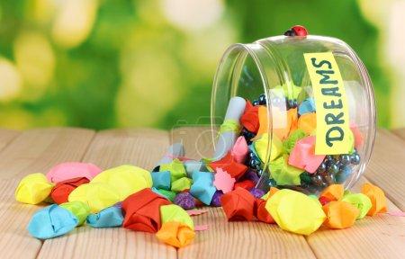 Photo pour Vase en verre avec étoiles en papier avec rêves sur table en bois sur fond naturel - image libre de droit