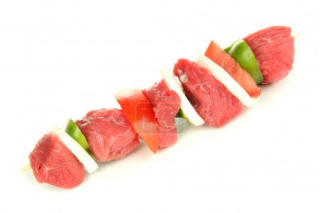 Raw beef meat and vegetables on skewer isolated on white