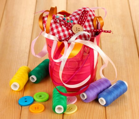 Color bucket with multicolor ribbons and thread on wooden background