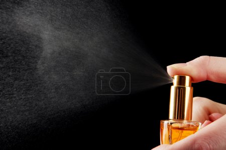 Photo for Women's perfume in bottle and spraying, on black background - Royalty Free Image