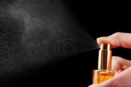 Photo pour Parfum féminin dans la bouteille et la pulvérisation, sur fond noir - image libre de droit