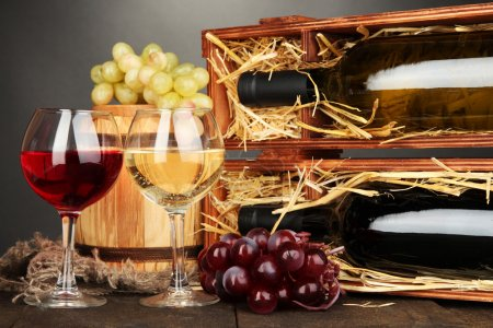 Wooden case with wine bottles, barrel, wineglasses and grape on wooden table on grey background