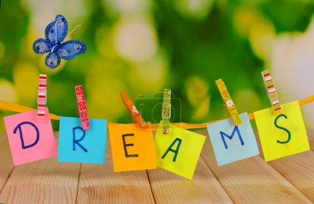 Photo for The word Dreams on wooden table on natural background - Royalty Free Image