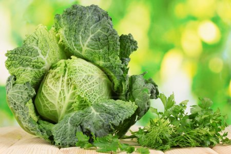 Fresh savoy cabbage on wooden table on natural background