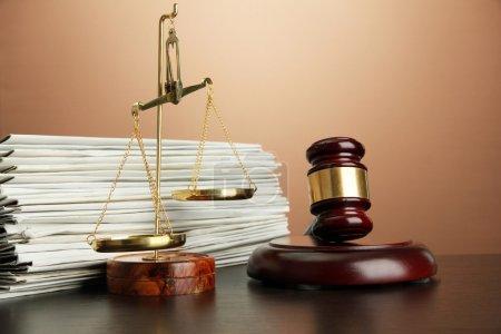 Photo pour Balance d'or de la justice, marteau et dossiers sur fond marron - image libre de droit