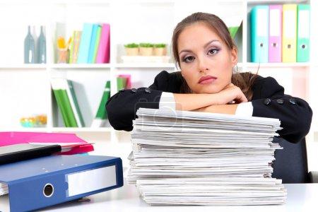 Photo pour Femme d'affaires triste avec des documents dans son lieu de travail - image libre de droit
