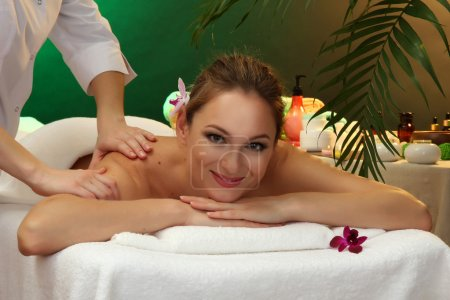 beautiful woman in spa salon with stones getting massage, on green background