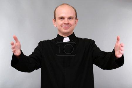 Photo pour Jeune prêtre sur fond gris - image libre de droit