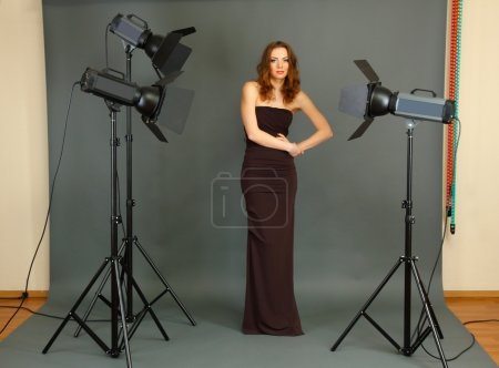 Beautiful professional female model resting between shots in photography studio shoot set-up