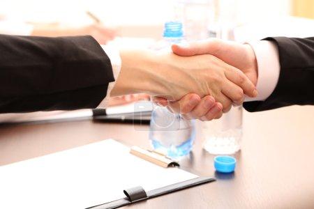 Photo pour Business serrant la main, sur fond de bureau - image libre de droit