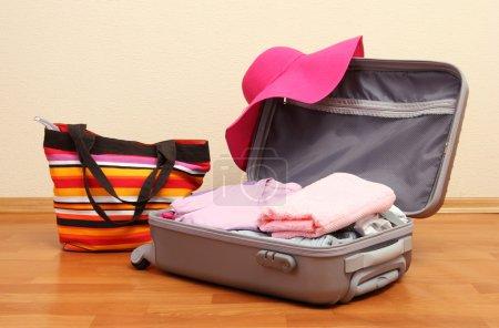 Photo pour Valise ouverte en argent avec vêtements dans la chambre - image libre de droit
