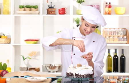 Young woman chef cooking cake in kitchen