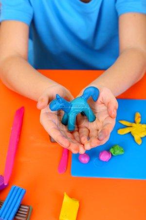 Photo pour Mains de l'enfant tenant hourse de pâte à modeler artisanale sur Bureau - image libre de droit