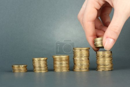Photo for Hand holding coins on grey background - Royalty Free Image