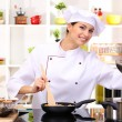 Young woman chef cooking in kitchen...