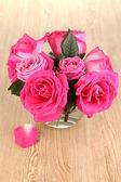 Krásné růžové růže ve váze na dřevěný stůl detail