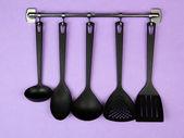 černá kuchyně nádobí na stříbrné háčky na fialovém pozadí