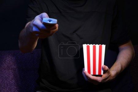 Photo pour Main de l'homme tenant une télévision à télécommande et du maïs soufflé, sur fond foncé - image libre de droit