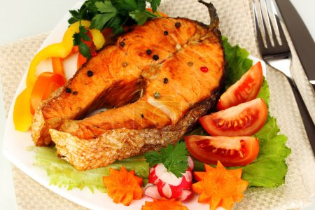 Appetizing grilled salmon with vegetables close up
