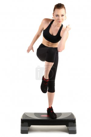 Photo for Young woman doing fitness exercises on stepper isolated on white - Royalty Free Image