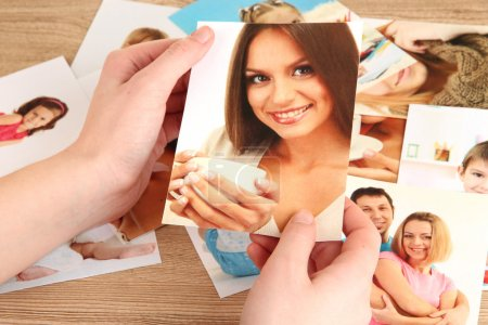 Photo for Photos in hands on wooden table - Royalty Free Image