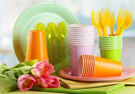 vaisselle de plastique multicolore sur table avec tulipes bouchent