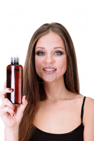 Woman with long hair holding bottle of shampoo, isolated on white