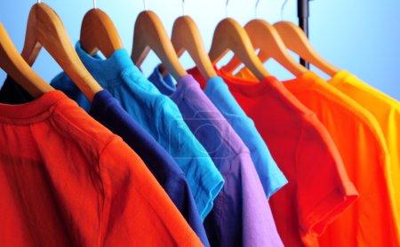 Photo pour Beaucoup de T-shirts sur cintres sur fond bleu - image libre de droit
