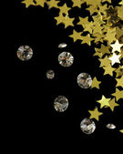 Beautiful shining crystals (diamonds) and golden stars, on black background