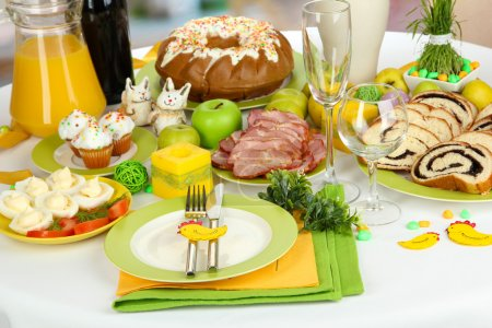 Serving Easter table with tasty dishes on room background