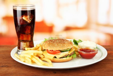 Photo for Tasty cheeseburger with fried potatoes and cold drink, on bright background - Royalty Free Image