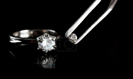 Shining crystal (diamond) in the tweezers and ring, on black background
