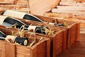 Láhve starého červeného vína v dárkové dřevěné krabičce, na kamenné pozadí