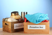 Donation boxes with clothing and food on blue background close-up
