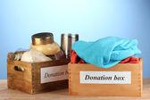 Cajas de donación con ropa y comida en primer plano de fondo azul