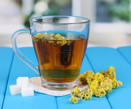 A cup of tea with immortelle on blue wooden table ...