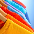 Lots of T-shirts on hangers on blue background...