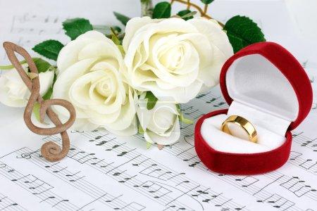 Photo pour Clé de sol, de roses et de boîte tenant la bague de mariage sur fond musical - image libre de droit