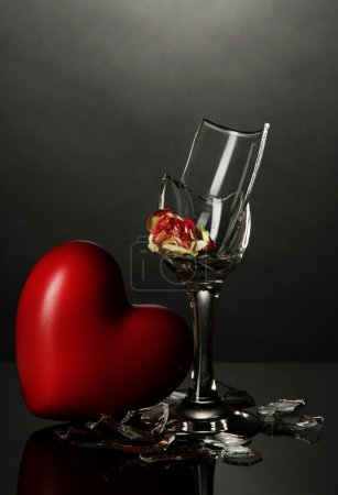 Broken wineglass and heart on grey background