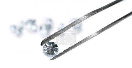 Photo pour Beau cristal brillant (diamant) dans la pince à épiler, isolé sur blanc - image libre de droit