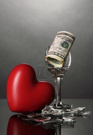 Broken wineglass, heart and money on grey background