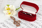 Treble clef, flower and box holding wedding rings on musical background