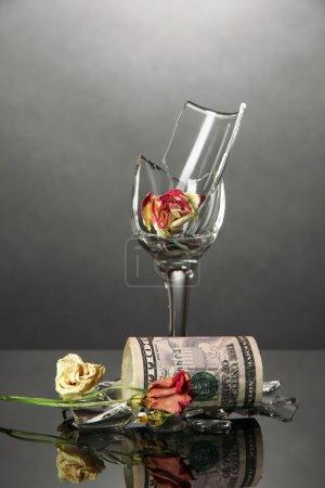 Broken wineglass and money on grey background