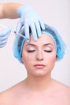 Photo pour Femme en clinique de beauté se faire injecter du botox, isolé sur blanc - image libre de droit