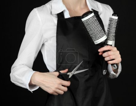 Hairdresser in uniform with working tools, isolated on black