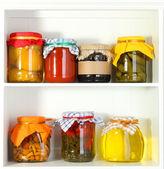 Homemade preserves on beautiful white shelves