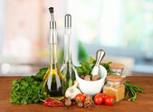 Composition of mortar, bottles with olive oil and vinegar, and green herbals, on bright background