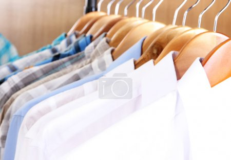 Photo for Men's shirts on hangers in wardrobe - Royalty Free Image