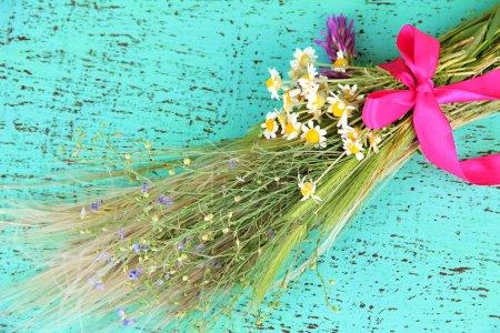 Strauß von Wildblumen und Kräutern, auf farbigem Holzgrund